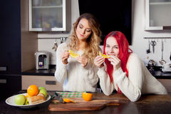Two young girls in the kitchen talking and eating Stock Images