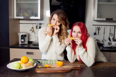 Two young girls in the kitchen talking and eating Royalty Free Stock Photos