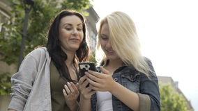 Two young girls laughing and scrolling touchscreen of smartphone looking at something funny on social media. Two young girls laughing and scrolling touchscreen stock video