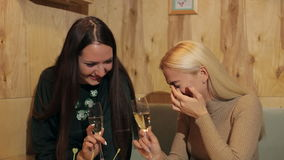 Two young girls laughing and sitting in a cafe with champagne. Bachelorette party stock video