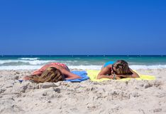Two Young Girls Laying On A Sunny Beach On Vacation Or Holi Royalty Free Stock Photography