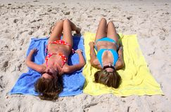 Two Young Girls Laying On A Sunny Beach On Vacation Or Holi Royalty Free Stock Photo