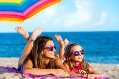 Two young girls laying together on beach. Stock Photos