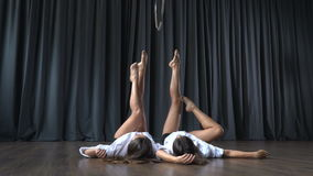 Two young girls lays on floor and stretches before making tricks on aerial hoop stock footage