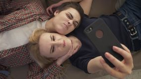 Two young girls lie on the couch, do selfie on a smartphone, grimace, make funny faces, top shot 60 fps. 4k stock video footage