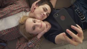 Two young girls lie on the couch, do selfie on a smartphone, smiling, lovers, lgbt, young couple, top shot 60 fps. 4k stock video