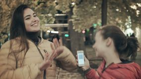 Two young girls listen to music on headphones in the middle of the street. Mom and daughter dance listening to songs in. Headphones. Close-up stock footage