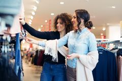 Two young girls look at clothing in store Royalty Free Stock Photography