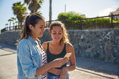 Two young girls looking at cellphone Royalty Free Stock Images