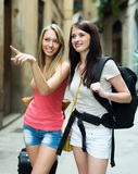 Two young girls with luggage smiling. Focus on brunette girl Stock Photography
