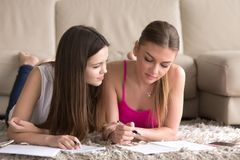 Two young girls lying on carpet, taking notes in notepads. Stock Photography