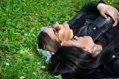 Two young girls lying down on the blanket and talking in a green meadow on a spring day in nature. Girl wear sunglasses and a black jacket. Relaxation and stock photography