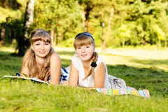 Two young girls are lying down on grass in the park enjoying summer, smiling and looking at camera. Royalty Free Stock Photography