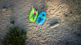 Two young girls are lying down on the sandy beach. Two young girls are lying down on the sandy beach during sunset. Aerial view from drone, top view Royalty Free Stock Image