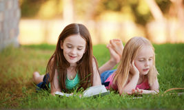 Two young girls lying on the grass outdoors reading a book.  The Stock Photo