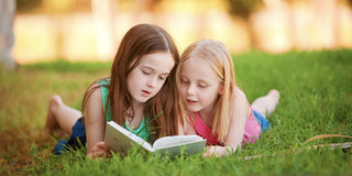 Two young girls lying on the grass outdoors reading a book.  The Stock Photography