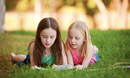 Two young girls lying on the grass outdoors reading a book.  The Stock Images