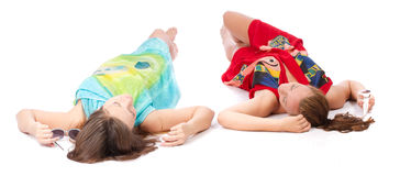 Two young girls lying and tan. On white background Stock Photo