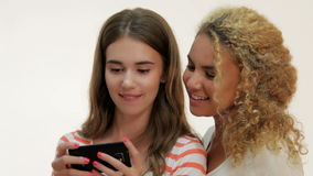 Two young girls make selfie. Brown-haired caucasian and red-haired mulatto make selfie with mobile phone. Two girls on a white background. Two women stay and stock footage