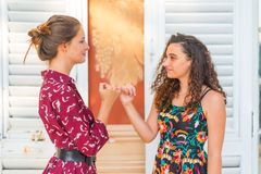 Pinky swear. Two young girls making a pinky promise. Together promising to each other royalty free stock image