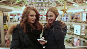 Two young girls at the Mall, looking with interest at the mobile phone screen. They are dressed in jackets. stock video