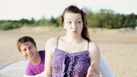 Two young girls and man dance on beach smile in camera. Sunny day. Vacation stock video