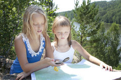 Two Young Girls   in Mountain read the Map near. Two Young Girls Tourists  in Mountain read the Map near  River Royalty Free Stock Photos