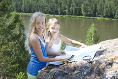 Two Young Girls   in Mountain read the Map near. Two Young Girls Tourists  in Mountain read the Map near  River Stock Photo