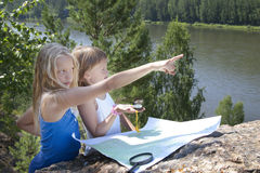 Two Young Girls   in Mountain read the Map near Stock Photos