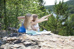 Two Young Girls   in Mountain read the Map near Stock Photography