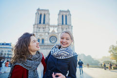 Two young girls near Notre-Dame in Paris royalty free stock images