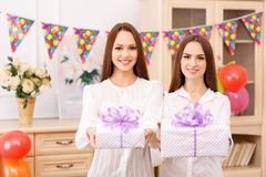 Two young girls are offering presents Royalty Free Stock Images