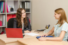 Two young girls in the office kindly look at each other Stock Photo