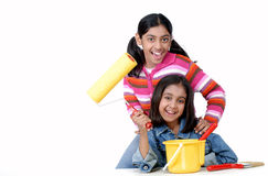 Two young girls with paint brush and roller Royalty Free Stock Image