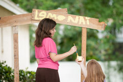 Two young girls painting a lemonade stand. Two young girls painting the sign of their lemonade stand. One girl holds the container of yellow paint while the Stock Image