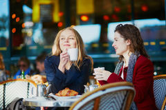 Two young girls in Parisian outdoor cafe. Drinking coffee with croissant and chatting. Friendship concept Royalty Free Stock Image