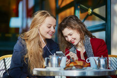 Two young girls in Parisian outdoor cafe Royalty Free Stock Images
