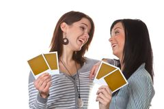 Two young girls with photos. Two friends have laughed with empty photos Stock Image