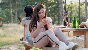Two young girls on a picnic looked at their phones with a dull look, while their boyfriend makes a fire and cooks for stock video footage