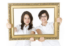 Two young girls with picture frame in front of them Stock Image
