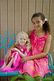 Two young girls in pink on blue bench stock photos