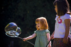 Two young girls play with bubbles. Two young girls playing with a bubble wand. Horizontally framed shot Stock Image