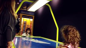 Two young girls playing air hockey table game stock video footage