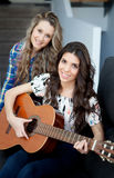 Two young girls playing guitar at home Stock Image