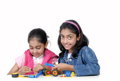 Two young girls playing with mechanical blocks Royalty Free Stock Images