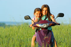 Two young girls playing outdoor on scooter Stock Images