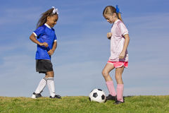 Two young girls playing soccer. Two young girls on youth soccer teams playing against each other Stock Image