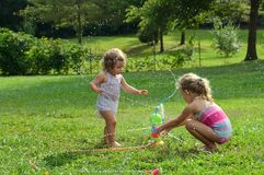 Two young girls playing with toy sprinkler Stock Image
