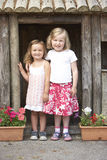 Two Young Girls Playing in Wooden House stock images