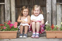 Two Young Girls Playing in Wooden House Royalty Free Stock Photos